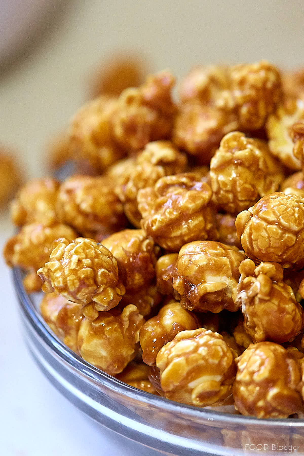 A side view of a glass bowl filled with delicious homemade caramel popcorn.