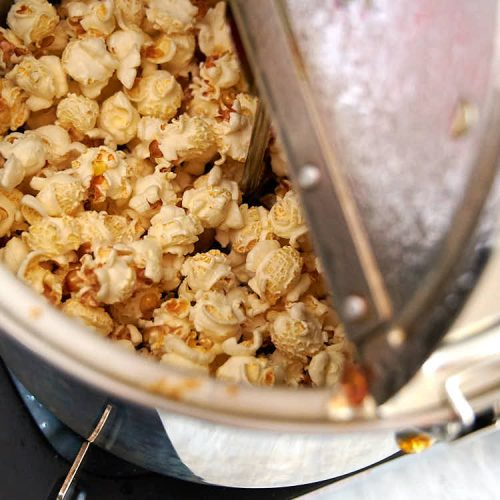 A partial view of a popcorn popper filled with mushroom popcorn just before making caramel popcorn.