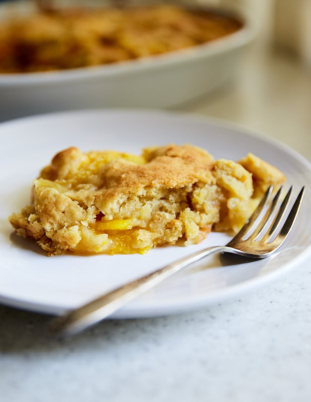 Ridiculously Easy Peach dump cake recipe! Also called peach crunch cake because of the crunchy crust. Delightful made with fresh peaches, and just as good made with canned peaches. Just dump peaches, cake mix and butter into a baking dish and bake. A cake recipe doesn't get any simpler than that.