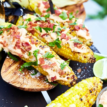 The best grilled corn on the cob comes from the simplest of the ingredients. Mayo, fresh garlic, bacon and salt is all you need. And some cayenne for a little heat. After grilling in husks, finish off with husks pulled back for more flavor. Sprinkle with lime juice and parsley and serve hot.