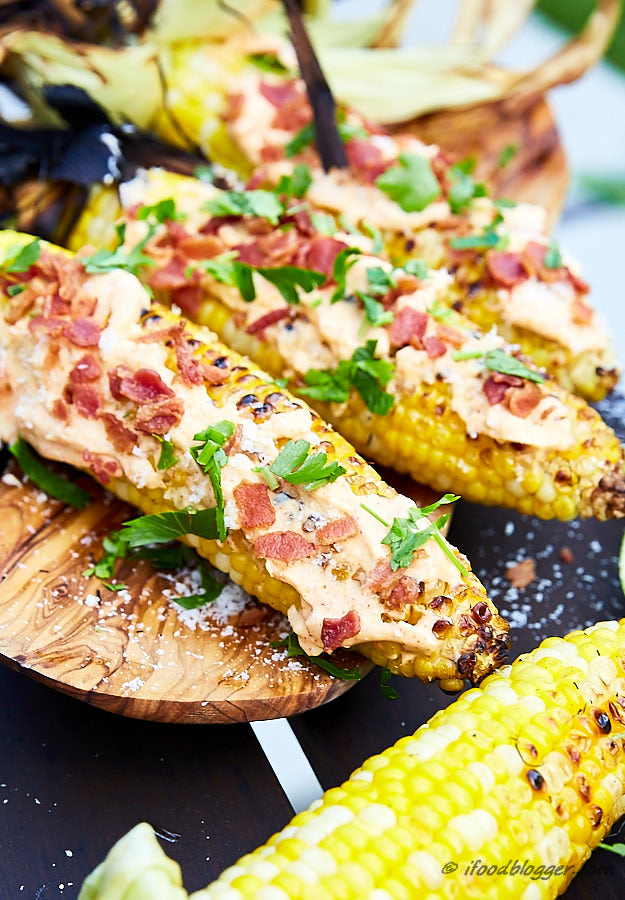 The best grilled corn on the cob comes from the simplest of the ingredients. Mayo, fresh garlic, bacon and salt is all you need. And some cayenne for a little heat. After grilling in husks, finish off with husks pulled back for more flavor. Sprinkle with lime juice, parmesan, and parsley. Serve hot.