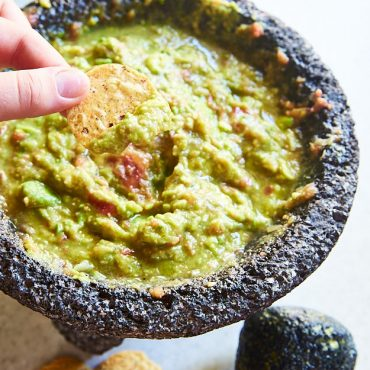 This homemade guacamole is made in a molcajete, a traditional Mexican mortar made of black lava rock. This is the best way to make authentic guacamole.