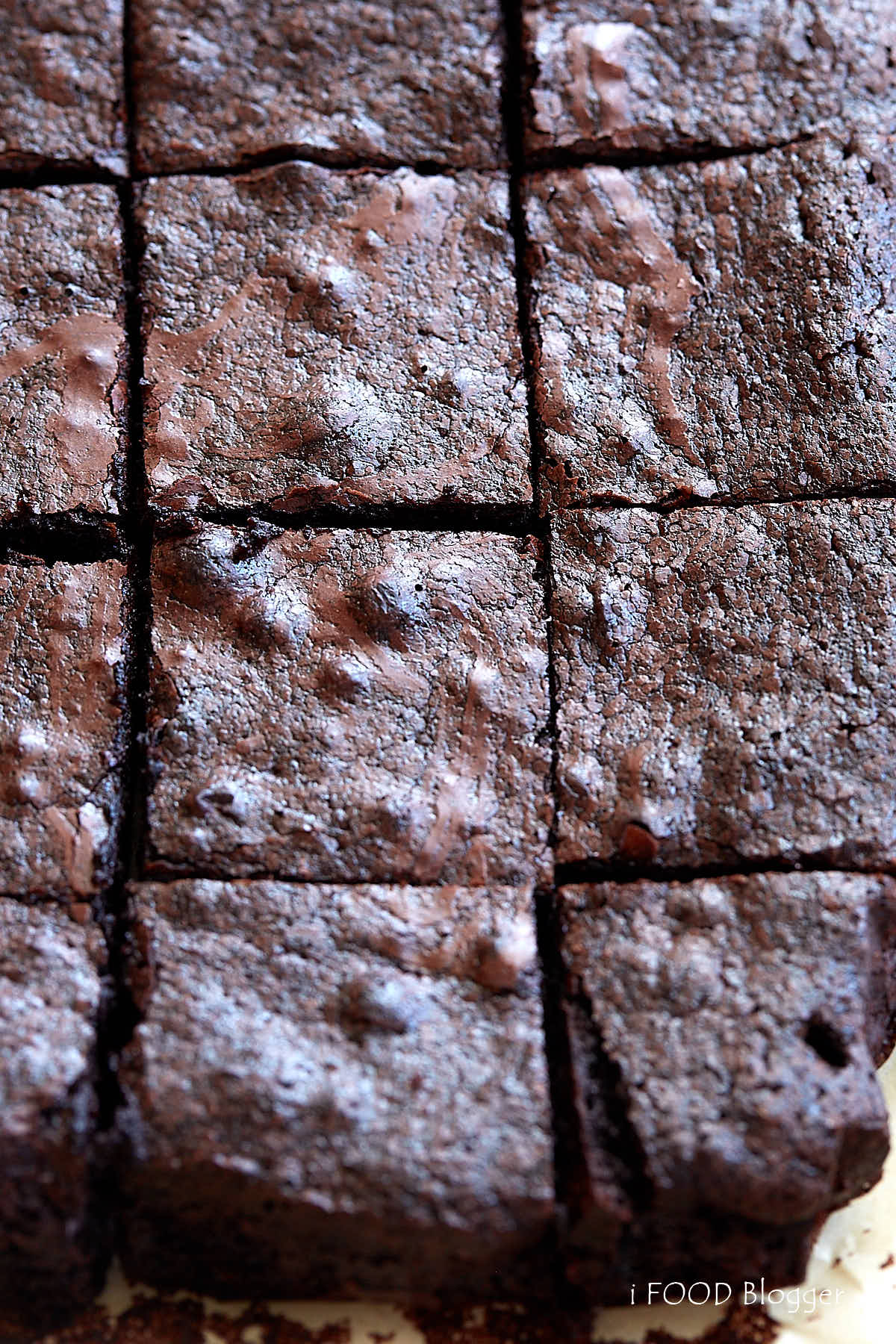 A top down view of a large from scratch, flourless brownie, cut into small pieces.