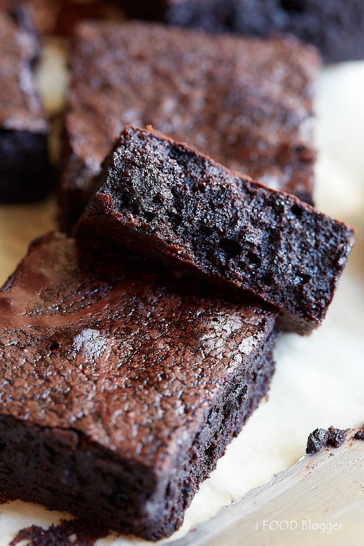 Brownies made from scratch, flourless and gluten-free, cut into pieces, set on a piece of paper.