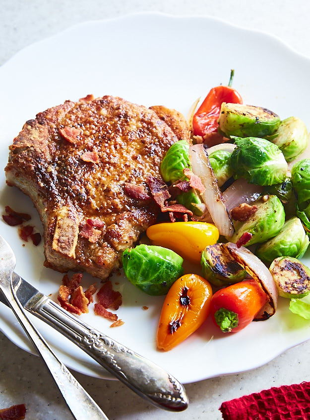 Quick and delicious pan-fried pork chops with bacon and sauteed Brussels sprouts, and peppers.