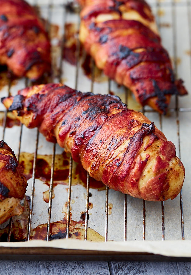 Bacon-wrapped chicken breasts on a baking sheet.