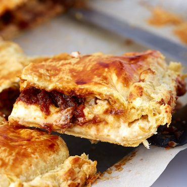This Kreatopita, a Greek Meat Pie, has a modern twist. It's made with chunks of beef stewed in dark ale and a layer of bechamel sauce. A must try!