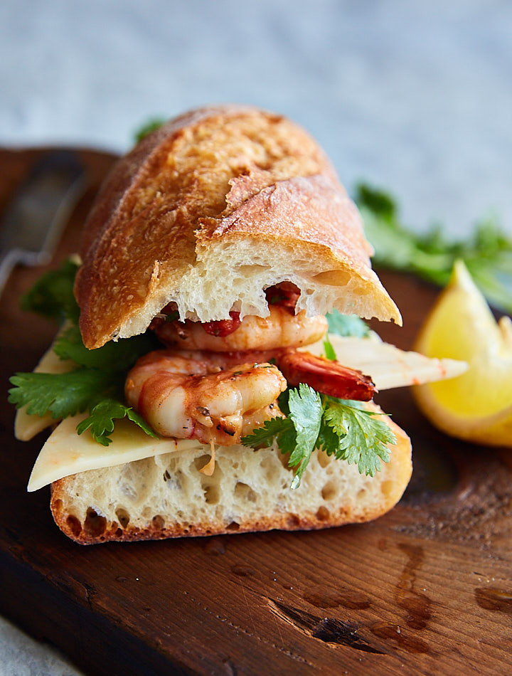 Shrimp sandwich made with grilled shrimp, freshly baked baguette, delicious shrimp dipping sauce, cilantro and spicy habanero jack cheese.