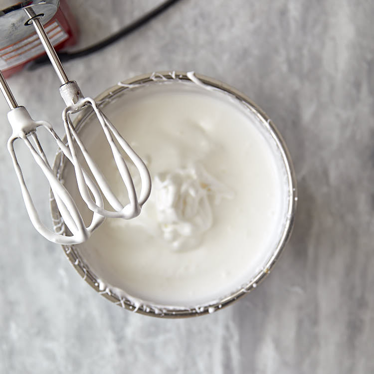Whip the egg whites to soft peaks, while adding granulated sugar very slowly while whipping.