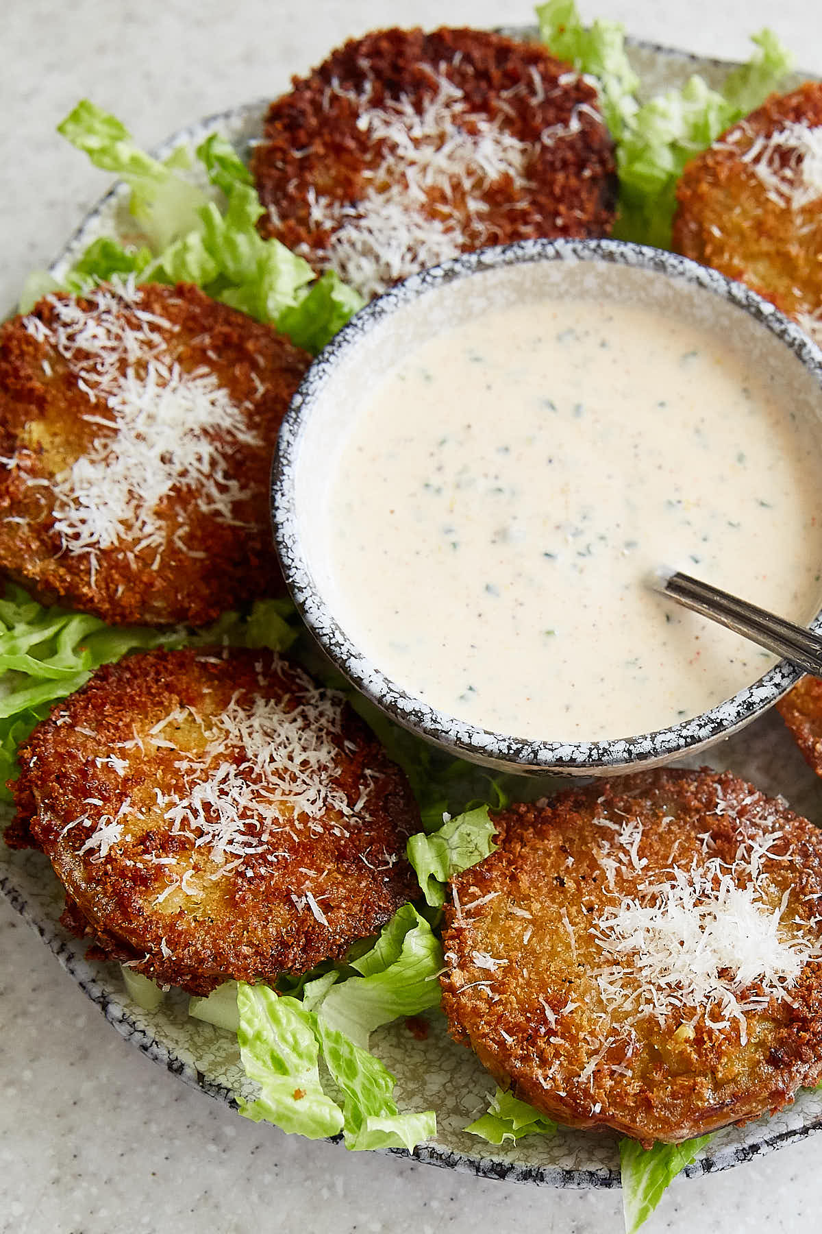 Fried Green Tomatoes on a platter with a bowl of dip in the middle.
