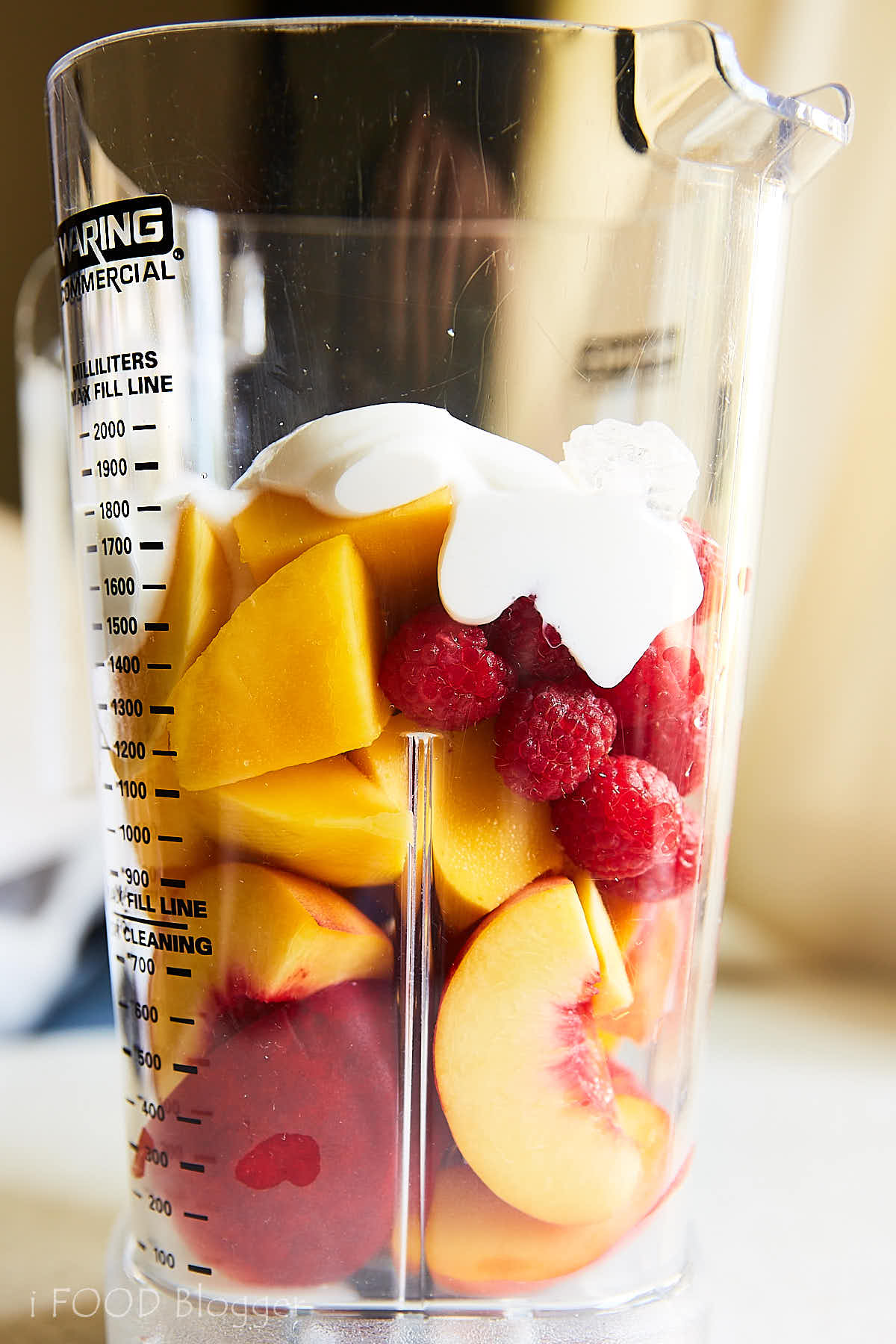 Delicious and healthy peach smoothie with raspberries and mango. Perfect for starting a day on a healthy note. | ifoodblogger.com