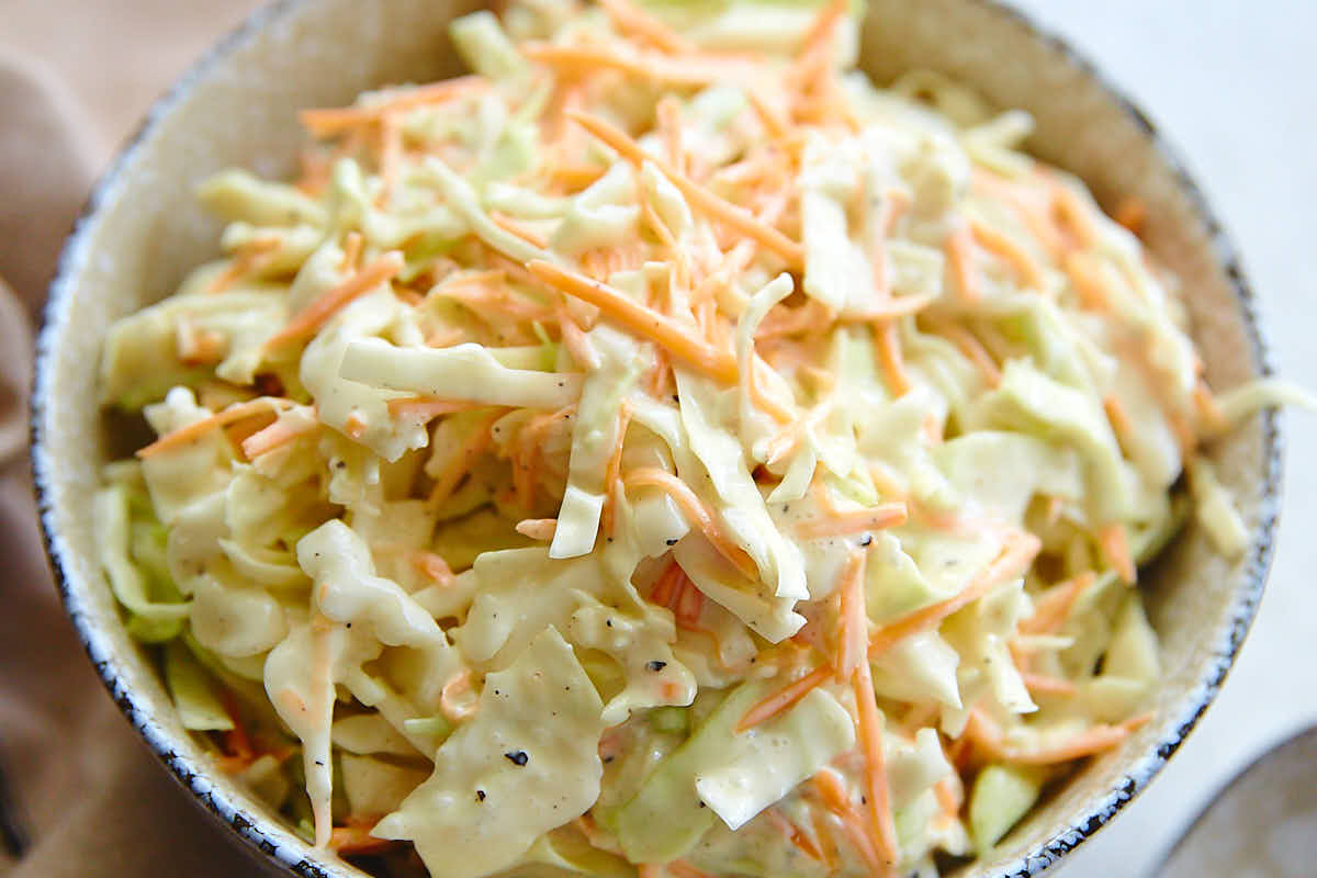 Top down close up view of a bowl filled with homemade coleslaw.