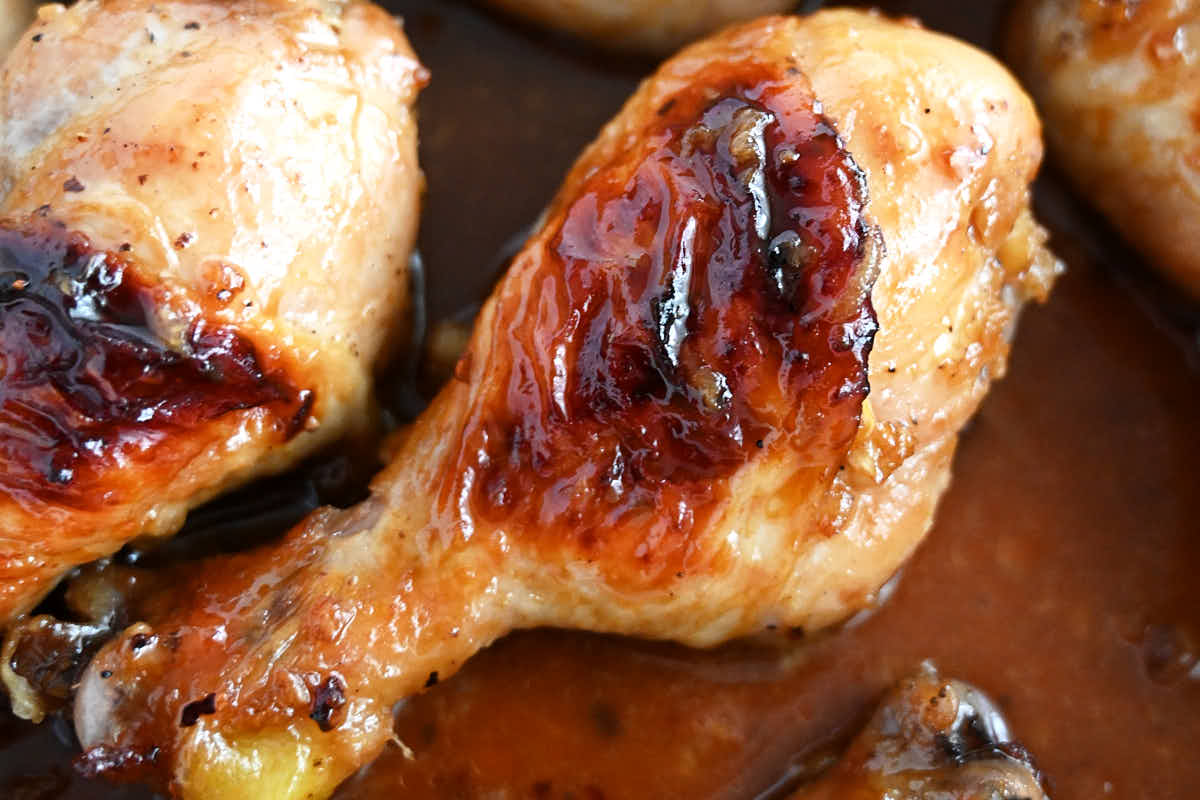 Baked chicken drumsticks, in a pan with sauce, golden brown color. Horizontal image.