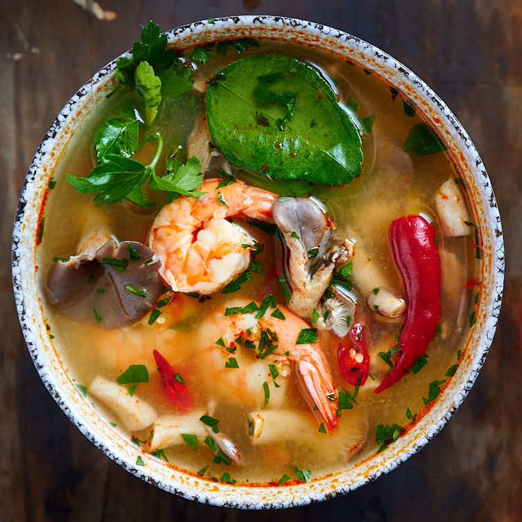 Top down view of Thai Tom Yum soup with plump shrimp, oyster mushrooms, bird eye chilies, lime leaves and cilantro.