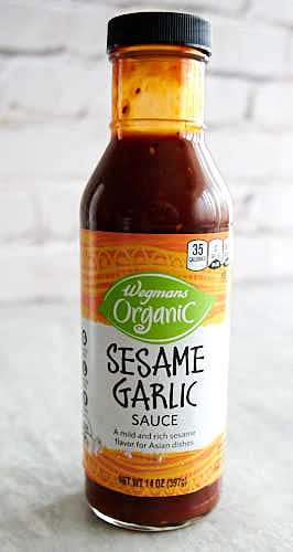 Asian sesame garlic sauce in a bottle on a table.