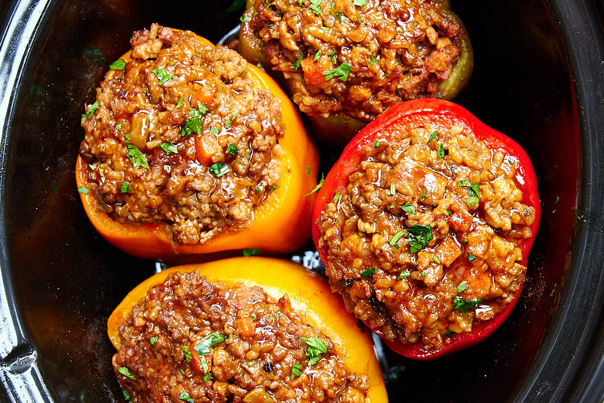 Four stuffed bell peppers inside a slow cooker.